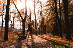 Young ballerina is dancing in the autumn park in the morning Royalty Free Stock Image