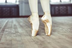 Feet in Pointe shoes on the floor. Young ballerina dancing, closeup on legs and shoes, standing in pointe position royalty free stock images