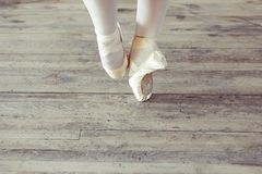 Feet in Pointe shoes on the floor. Young ballerina dancing, closeup on legs and shoes, standing in pointe position stock photo