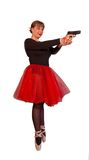 Young ballerina holds gun. Young attractive woman in black-red ballerina dress holds black gun by two hands on isolated background Royalty Free Stock Photography