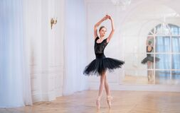 Free Young Ballerina In A Black Tutu Is Dancing On Pointe In Large Bright Hall In Front Of A Mirror Stock Image - 202077821