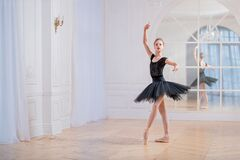 Free Young Ballerina In A Black Tutu Is Dancing On Pointe In Large Bright Hall In Front Of A Mirror Stock Photos - 202538833