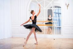 Free Young Ballerina In A Black Tutu Stands In Graceful Pose On Pointe Shoes In A Large Bright Hall In Front Of A Mirror Royalty Free Stock Images - 199670719