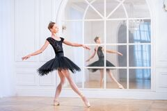 Free Young Ballerina In A Black Tutu Stands In Graceful Pose On Pointe Shoes In A Large Bright Hall In Front Of A Mirror Royalty Free Stock Images - 199670789