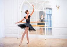 Free Young Ballerina In A Black Tutu Stands In Graceful Pose On Pointe Shoes In A Large Bright Hall In Front Of A Mirror Stock Photography - 202089022