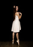 Young ballerina with a perfect body is dancing in pointe shoes on dark background Stock Image