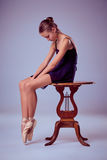 Young ballerina sitting on wooden chair Royalty Free Stock Images