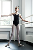 Young ballerina standing at ballet barre royalty free stock photo