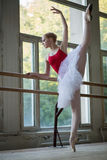 Young ballerina standing on one leg on your toes in pointe and d Stock Photos