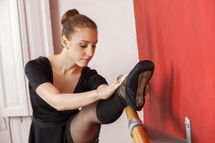 Young Ballerina Stretching Her Leg At Barre Royalty Free Stock Photography