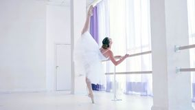 Young ballerina is training ballet element near the barre stand in dance class. Professional ballet dancer in white tutu and pointes is training ballet element stock image