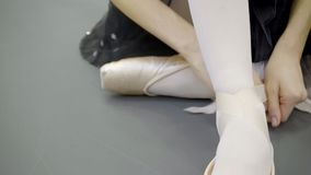 Young ballerina is tying tape of pointe shoes in modern studio. Attractive lady ties ribbon of footwear sitting on floor in light room. Beautiful dancer in stock video footage