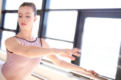 Young Ballerina Warming Up in Sunny Studio Stock Images
