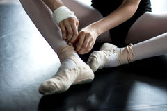 Young ballerina wearing ballet slippers. Young ballerina is wearinf her ballet slippers in the dance class during the training. Ballerina`s feet royalty free stock photos