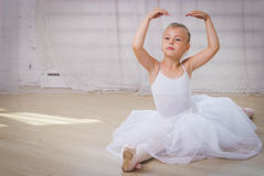 Young ballerina in white clothes sitting on the floor Royalty Free Stock Photography