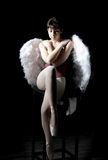 Young ballerina. With wings sitting in dark studio Stock Photo