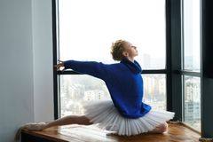 Ballerina in woolen sweater. Young ballerina in woolen sweater and ballet tutu dances by window royalty free stock photo