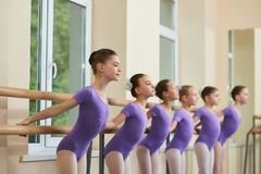 Young ballerinas doing exercises at barre. Group of young beautifull ballet dancers performing ballet elements in ballet studio Stock Image
