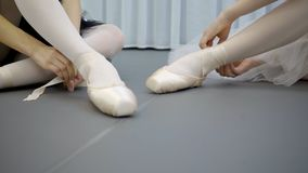 Young ballerinas dressing pointes, sitting in ballet studio. Two women are on floor, they putting professional footwear for dance, tie satin tape to ankle stock footage