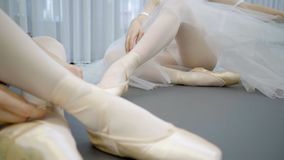Young ballerinas are dressing pointes sitting on floor in modern studio. Two women tying tape of pointe shoes indoors. Elegant dancers in classic silk costumes stock footage