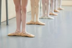 Young ballerinas legs in basic position. Group of little ballerinas standing in ballet position, cropped image. Classic ballet position stock photo