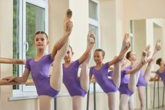 Young ballerinas legs lift in studio. Group of young ballerinas holding legs in extension at ballet barre. Ballet girls having practice stock images