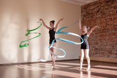 Young ballerinas in motion. Rhythmic gymnastics. Teenage sport, healthy teen lifestyle. Pretty girls with flying ribbons, dance class background, ballet stock image