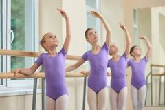 Young ballerinas rehearsing in ballet class. Group of young ballerinas performing different choreographic exercises at ballet barre royalty free stock photo