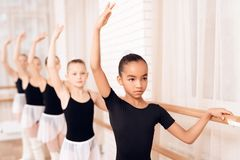 Young ballerinas rehearsing in the ballet class. They perform different choreographic exercises. They stand in different positions near the ballet barr royalty free stock image