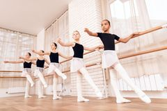 Young ballerinas rehearsing in the ballet class. They perform different choreographic exercises. They stand in different positions near the ballet barr stock photography