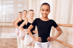 Young ballerinas rehearsing in the ballet class. They perform different choreographic exercises. They stand in different positions near the ballet barr royalty free stock photo