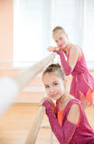 Young ballerinas resting at barre in class Royalty Free Stock Photo