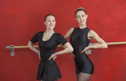 Young Ballerinas Smiling Against Red Wall Stock Photo