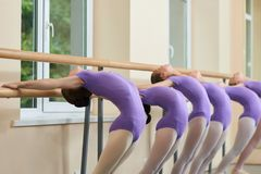 Young ballerinas stretching at ballet barre. Group of ballet dancers stretching backs at ballet barre. Flexibility and efforts Royalty Free Stock Photos