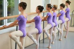 Young ballerinas training at ballet barre. Group of ballet dancers posing near barre in ballet studio. Difference between gymnastics and ballet Stock Images