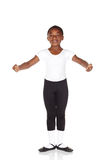 Young Ballet Dancer. Young African ballet boy on white background and reflective white floor showing various ballet steps and positions. Not Isolated Stock Photo