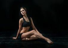 Young ballet dancer dansing on black background Stock Images