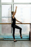 Young ballet dancer exercising at the barre in. Young female ballet dancer exercising at the barre by the window in studio. Ballet classes royalty free stock images