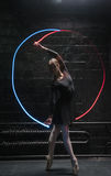 Young ballet dancer performing with a gymnastic ribbon. Ballerina dancing . Concentrated graceful young ballet dancer standing in front of the dark wall on Stock Images
