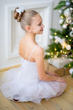 Young ballet dancer sitting near Christmas tree. On the wooden floor Royalty Free Stock Photo