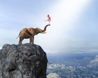 Surreal Dancing Team, Teamwork, Ballet. A young ballet dancer stands on an elephant trunk on a cliff in a surreal mountain cliff landscape stock photo
