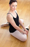 Young ballet dancer stretching on the floor Stock Photo