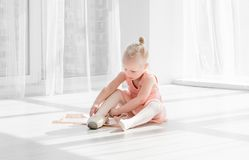 Young ballet dancer in tutu sitting on the floor and tying pointe shoes. Beautiful young ballet dancer in tutu sitting on the floor in white light room and tying royalty free stock image