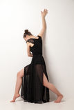 Young ballet dancer wearing black transparent dress dancing. Over white background Royalty Free Stock Image