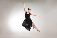 Young ballet dancer wearing black transparent dress jumping Stock Photos