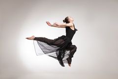 Young ballet dancer wearing black transparent dress jumping Royalty Free Stock Photography