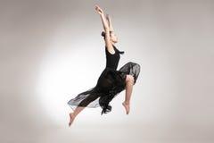 Young ballet dancer wearing black transparent dress jumping Royalty Free Stock Photos