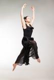Young ballet dancer wearing black transparent dress jumping Stock Images