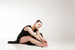 Young ballet dancer wearing black transparent dress sitting on floor. Over white background stock image