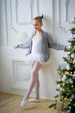 Young ballet dancers learning the lesson near Christm. Young ballet dancers learning the lesson near the wall. Try some new pose Stock Photo